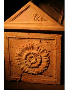 Rosette and sculptured top on a red limestone sarcophagus.